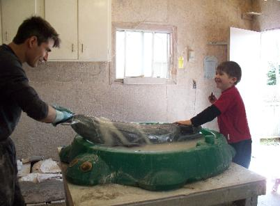 Father and son wet-sanding a marble sculpture of a Blue whale